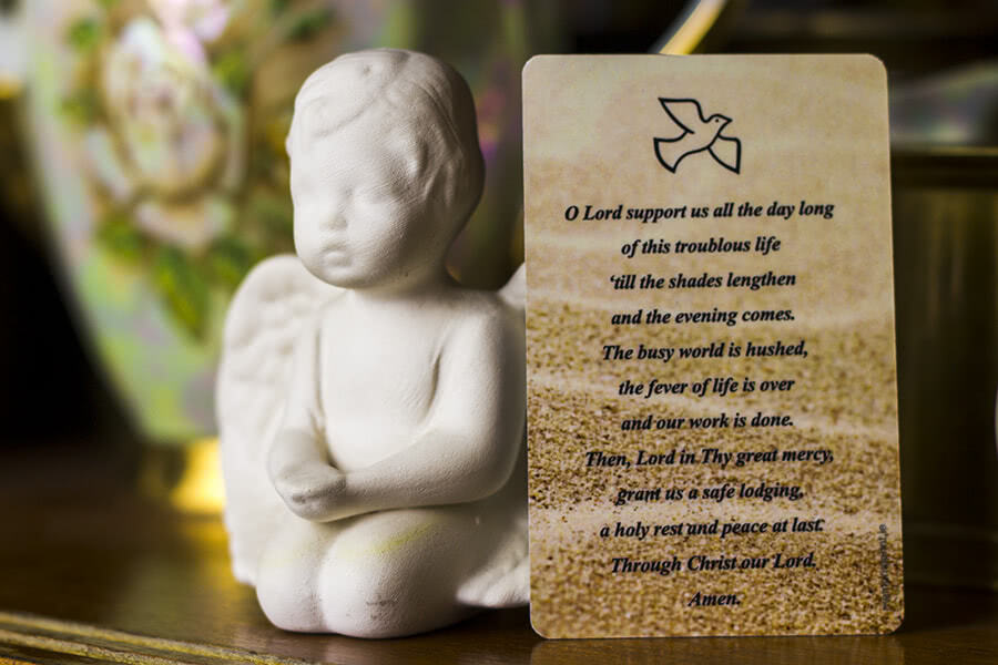 Card with O Lord support us prayer next to small angel figure.