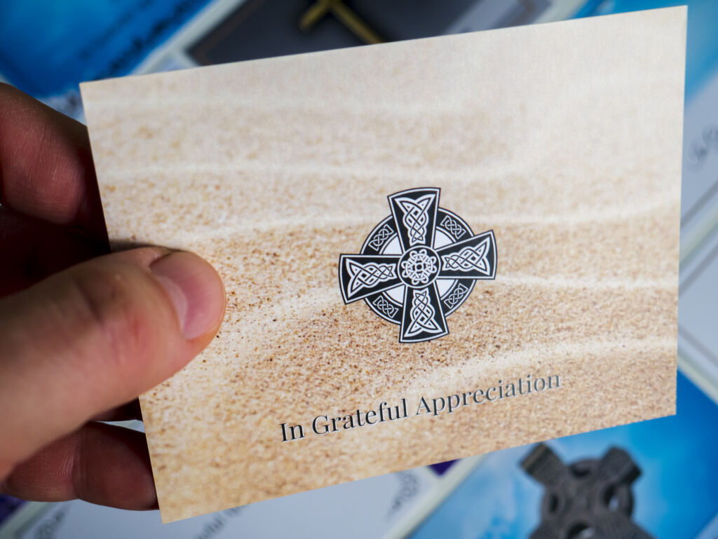 Front of a double sided acknowledgement card with sand pattern background and black decorative Irish/Celtic cross