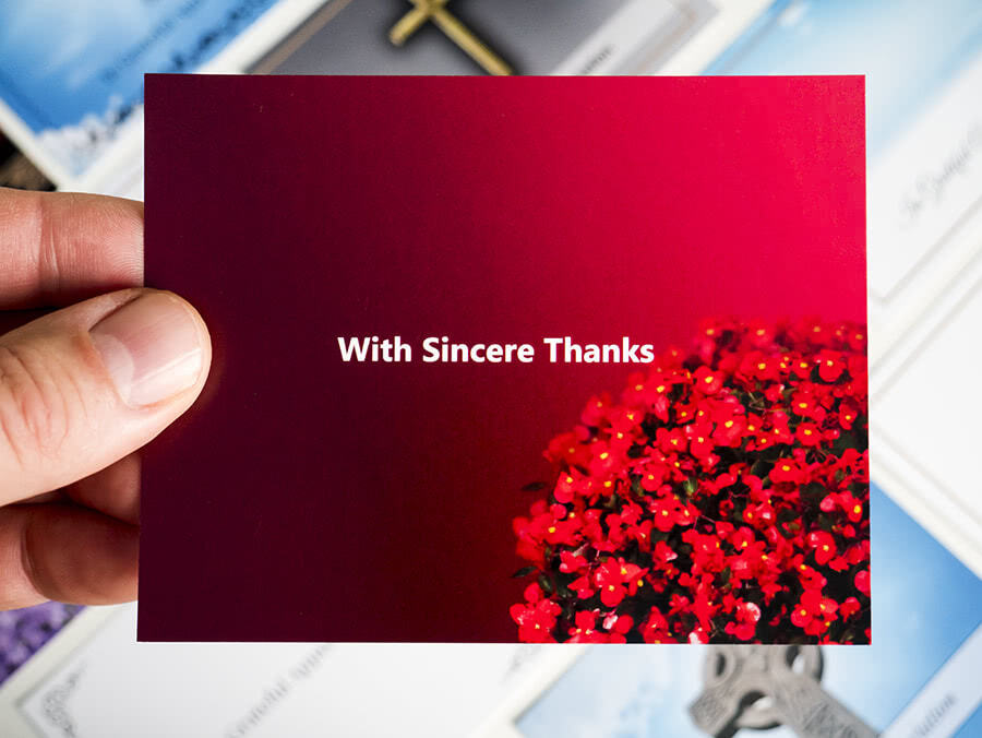 "Red acknowledgement card with bunch of flowers in the corner and ""With Sincere Thanks"" writing in the center."
